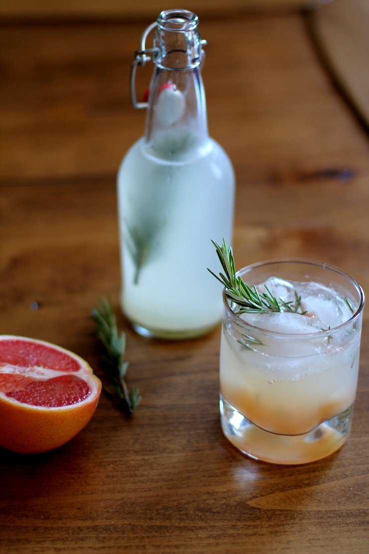 A glass of grapefruit ginger beer on a table with a bottle in the background and half of a grapefruit and sprigs of rosemary