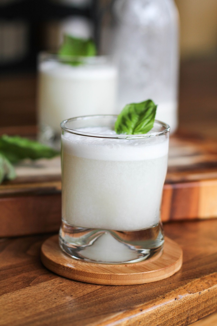 closeup glass of coconut basil ginger beer with a glass and bottle in the background