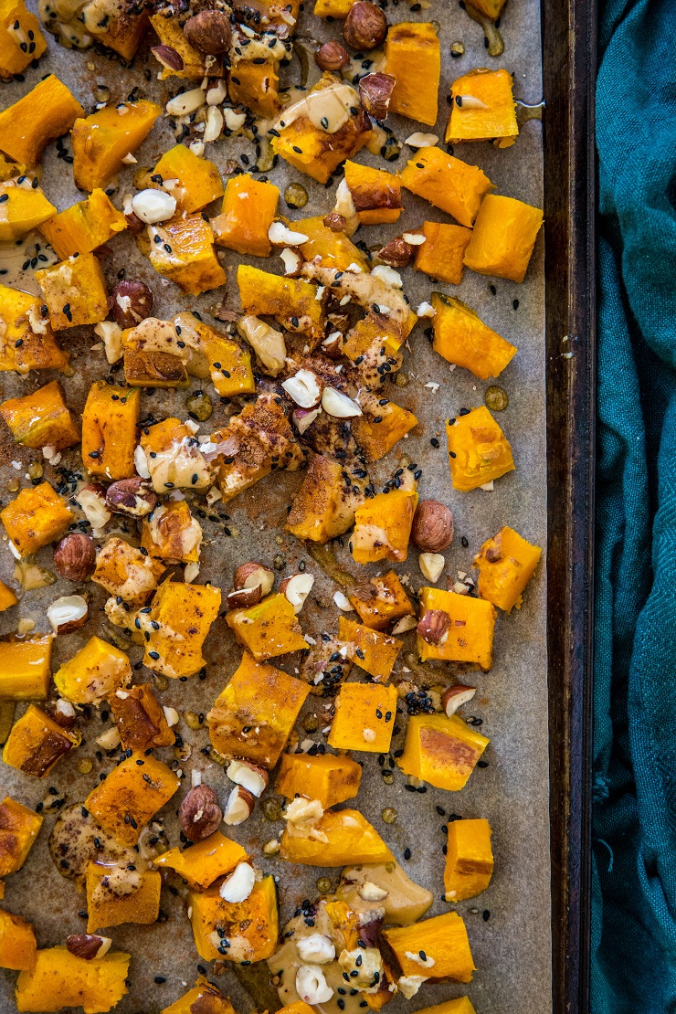 roasted kabocha squash with hazelnuts drizzled with maple tahini on a baking sheet with a dark blue napkin