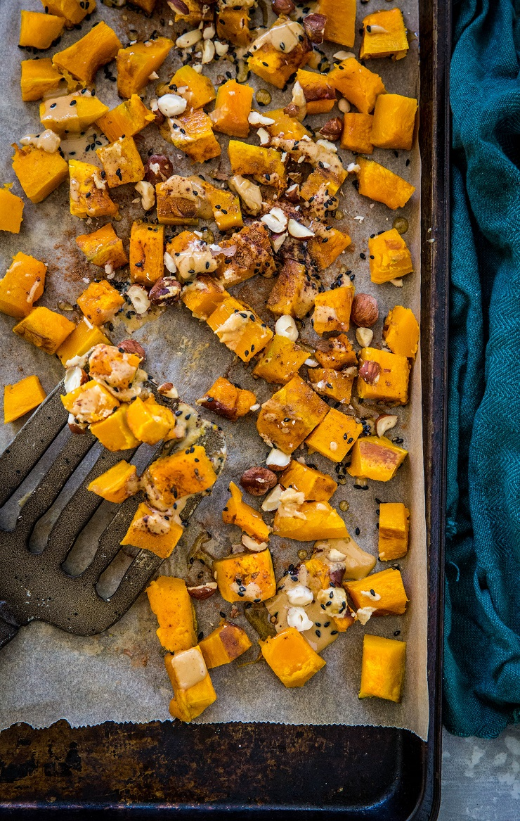 Baking sheet with roasted kabocha squash drizzled in cinnamon tahini with a spatula and dark blue napkin