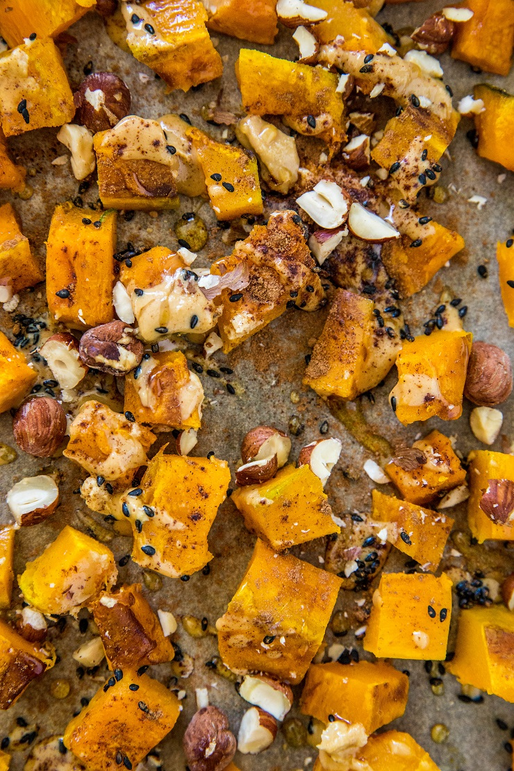 Close up photo of roasted kabocha squash on a baking sheet with tahini and hazelnuts